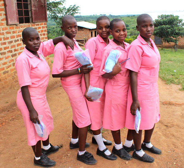 Girls in Uganda hold reusable menstrual pads, which they received after a reproductive health presentation at school.