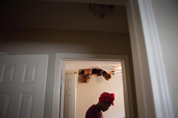 Teniya Brewer walks through Pauline Simpson's home looking at the water damage.