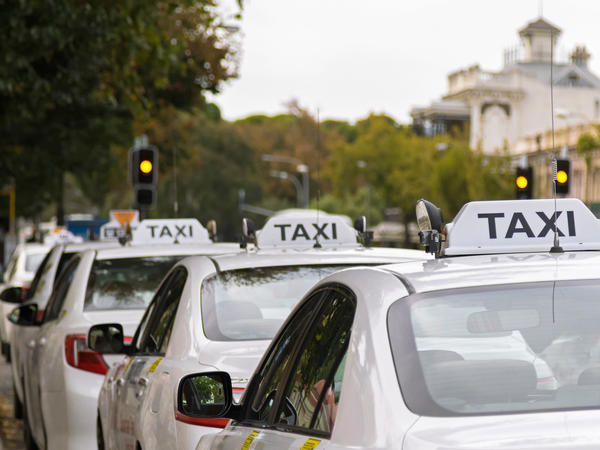 Taxis park along the footpath in Adelaide, Australia. Alva Noe asks: Do taxi apps make people interact less — or better — with their drivers?