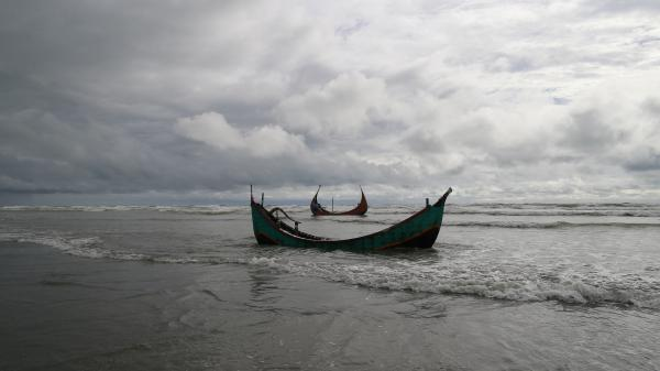 Two boats that capsized while carrying fleeing Rohingya, seen Thursday after they were recovered by Bangladeshi villagers. About two dozen bodies were also recovered, according to local officials.