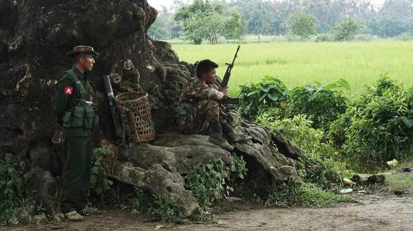 Myanmarese soldiers stand guard at a checkpoint in rural Rakhine state on Wednesday. Plumes of smoke reportedly billowed from several villages in the worst-hit section of the state as troops clashed with Rohingya militants this week.