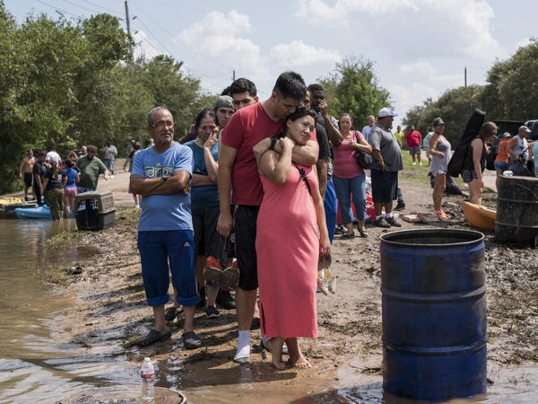Ellie Nizamutdinova is comforted by her partner, Arnulfo Moreno, while they wait in line for a boat ride to check on their flooded home along Barker Cypress road on the west side of Houston.