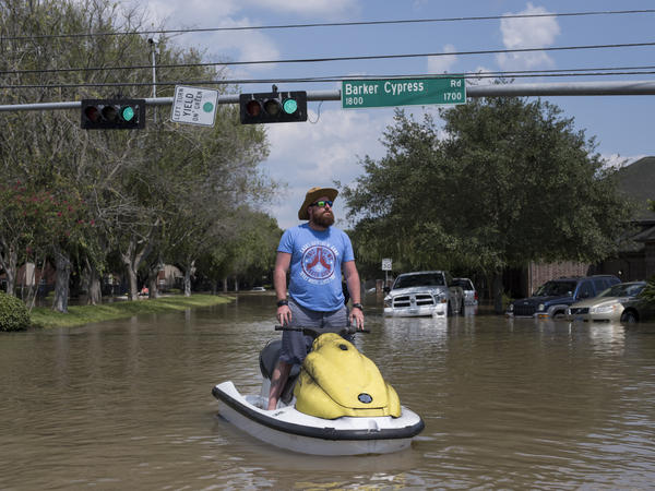 Rabon Raulerson stands on the personal watercraft he has been using to help flood victims on the west side of Houston check out their homes and salvage what they can.