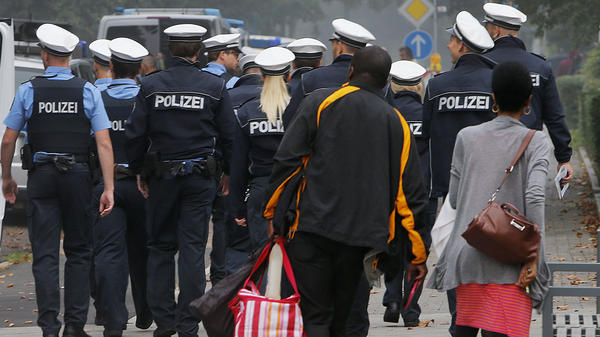 A couple leaves their apartment building and walks behind police during an evacuation of more than 60,000 people in Frankfurt on Sunday.