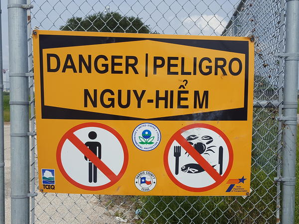 A sign along the San Jacinto River warns against eating fish or shellfish from the river. A nearby site that has been a source of toxins was flooded by Hurricane Harvey.