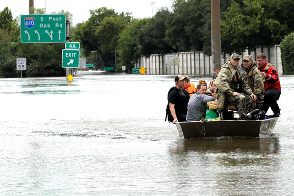 Residents are rescued from their homes surrounded by floodwaters. (David J. Phillip/AP)