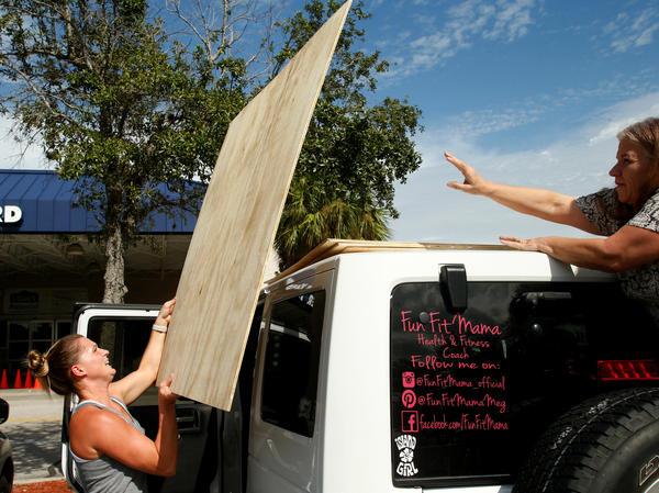 Megan Daniel (left) gets a hand from a stranger, Delene Cole, as she loads plywood she intends to use as storm shutters ahead of Irma on Tuesday in St. Petersburg, Fla.