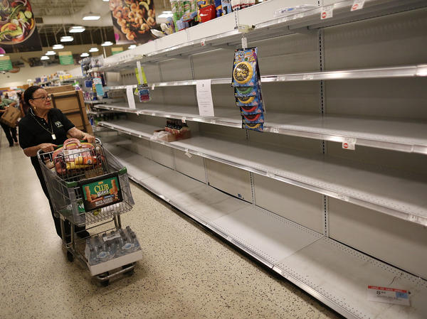 Grocery store shelves are barren after selling out of bottled water on Wednesday in Miami.