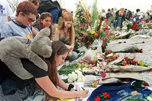Amber Johnson (left front) writes a note for the Columbine High School shooting victims with friends on April 26, 1999, at the memorial site in Clement Park in Littleton, Colo.