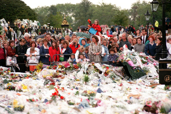 Thousands of mourners gather on Sept. 3, 1997, to lay flowers and cards atop the immense mound of flowers at the gates of Kensington Palace in London, the official residence of Diana, Princess of Wales.