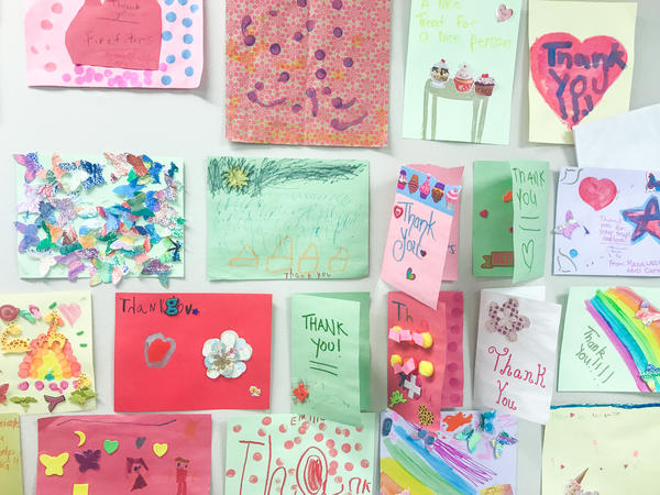 Thank you cards from children who received meals cooked by volunteer chefs on the wall at the kitchen.