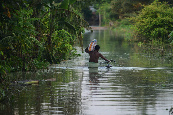 An Indian villager wades through floodwaters in West Bengal on Aug. 23.