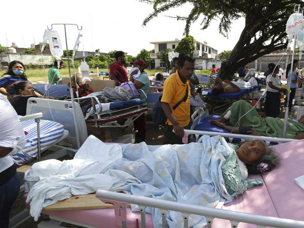 Evacuated patients lie on their hospital beds under a tree in Juchitan. At least 20 aftershocks followed the massive quake.