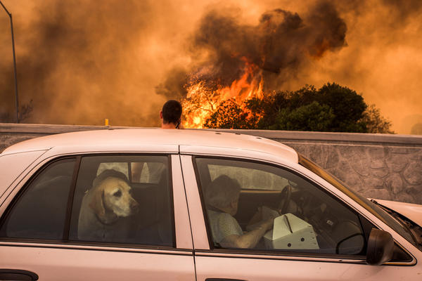 Residents of the community of Tujunga, Calif., flee a fire near Burbank on Sept. 2. Even people much farther from the flames are feeling health effects from acrid smoke.