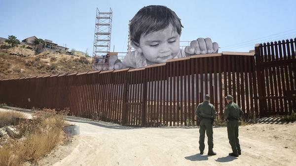 The boy glances down from the Mexican side at two Border Patrol officers, who return his stare from the U.S.