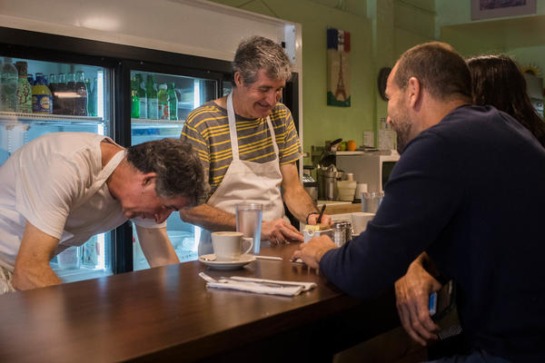 Café Croissant owners and twin brothers Didier (left) and Pascal Vedel serve customers in Miami on Saturday. They opened their doors Saturday morning at 7 a.m. with the plan to stay open until noon unless the weather encouraged them to close earlier.