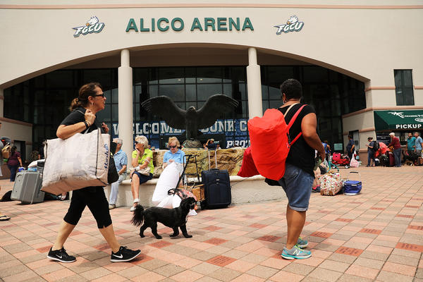 People arrive, many with their pets, at Alico Arena which is shelter thousands of Floridians hoping to ride out Hurricane Irma in Fort Myers, Fla., on Saturday.