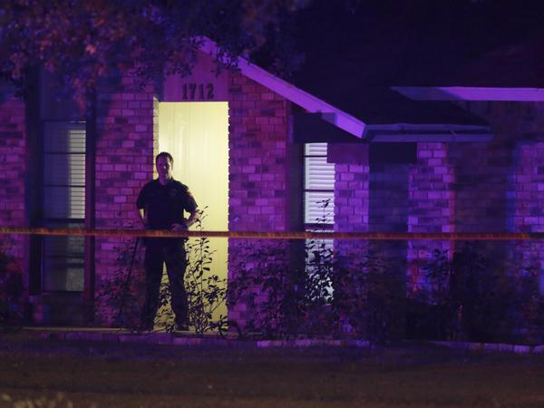 A police officer stands guard outside the scene of a mass shooting in Plano, Texas, on Sunday.