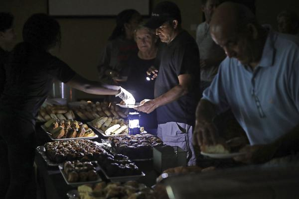 Hotel guests are served breakfast by lamplight as the power remains off at the Courtyard by Marriott one day after Hurricane Irma struck in Fort Lauderdale, Fla.