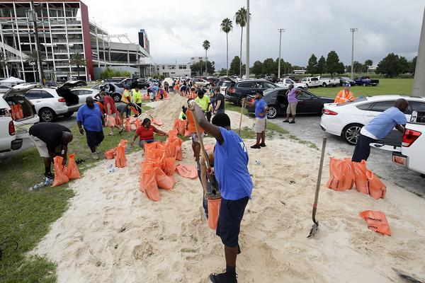 Orlando city employees and volunteers fill sandbags for residents as they prepare for Hurricane Irma, Friday, Sept. 8, 2017, in Orlando, Fla. Lines of vehicles stretched for miles and many waited several hours to get the sandbags. (AP Photo/John Raoux)