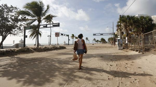 Hurricane Irma dumped water on towns and covered oceanside streets with sand in several states. Here, Amela Desanto walks on the sand-covered road along Fort Lauderdale Beach on Monday, as the storm headed inland.