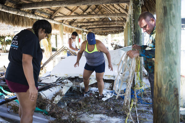 Mirna Narvaez (center) and her husband Miguel Lechuga (right) assess their family's commercial fishing boat after losing countless crab and lobster traps in Tavernier, Fla.