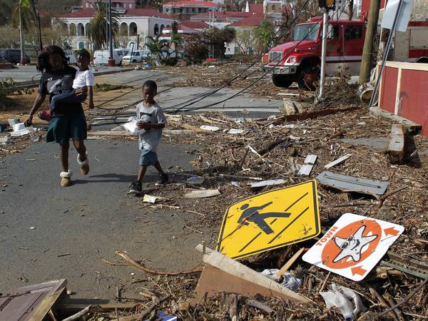 A woman and her two children pass the debris left of the streetside in St. Thomas, U.S. Virgin Islands, on Sunday.