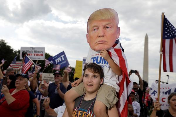 Gabriel Gunstin of Southern Township, Michigan, holds up his nephew, James Crockett, 9, with a Trump mask at the 'Mother of All Rallies.'