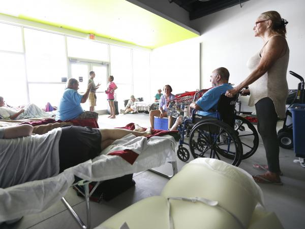 Evacuees at a special needs shelter sit and chat or rest, Thursday, Sept. 14, 2017, at Florida International University in Miami, Fla. About 30 people, including staff with the Florida Keys Outreach Coalition for the Homeless from Key West, Fla., were sheltered in a storefront underneath a parking garage on campus.