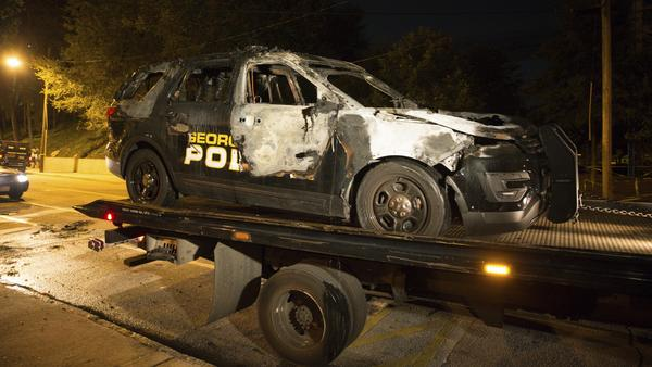 A burned-out Georgia Tech police vehicle sits on a truck outside a police station on the Atlanta campus on Monday night. The car was set ablaze during a protest over a deadly police shooting of a Georgia Tech student Saturday.