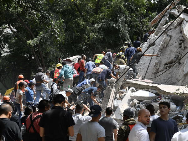 People remove the debris of a collapsed building as they look for possible victims after the 7.1 magnitude quake rattled Mexico City on Tuesday.