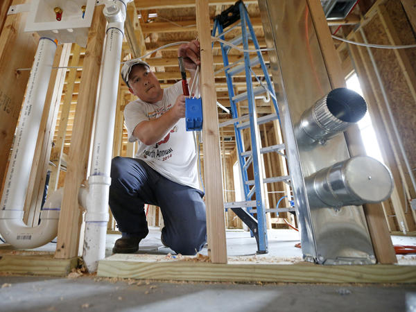 Electrician Chris Piazza works on a home being built in Destrehan, La., in March. The recent enormous storms have hit the housing industry hard, with several signs turning negative.