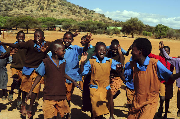 Children in Il Ngwesi, Kenya, horse around in their schoolyard.