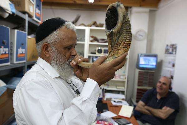 A Jewish man tests the sound of a shofar, a religious musical instrument made from a ram horn, before buying it at a Shofarot factory in Tel Aviv on Sept. 25, 2016, ahead of the Jewish New Year. (Menahem Kahana/AFP/Getty Images)