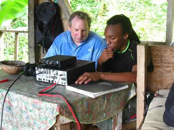 Brian Machesney (Call sign: K1LI), left, and Gordon Royer Jr. (J73GAR), in Dominica earlier this year, discussing the operation of a ham radio set.