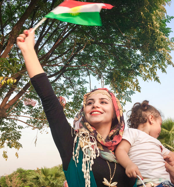 Rogesh Adnan Yasin, a Syrian Kurd, holds a Kurdish flag and her 2-year-old niece at a pro-referendum rally in Irbil, Iraq. Yasin believes that if Iraqi Kurds achieve independence, her Kurdish region of Syria will be next.