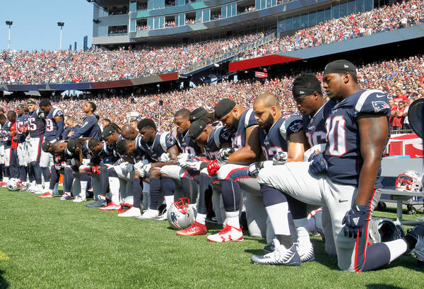 Members of the New England Patriots — and players across the league — kneel during the national anthem before Sunday's game against the Houston Texans.
