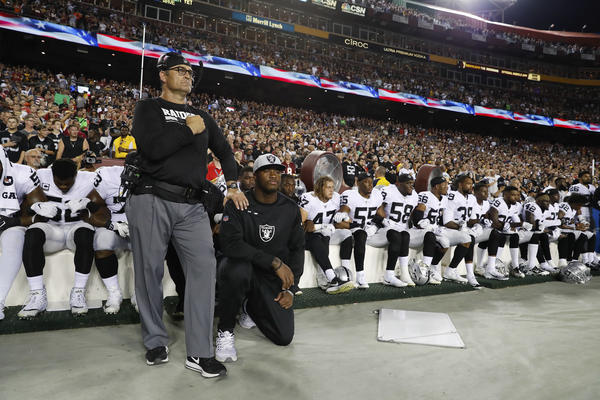 Members of the Oakland Raiders kneel during the national anthem before al game against the Washington Redskins in Landover, Md.