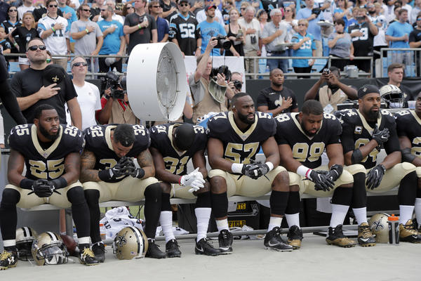 New Orleans Saints players sit on the bench during the national anthem before playing the Carolina Panthers in Charlotte, N.C.
