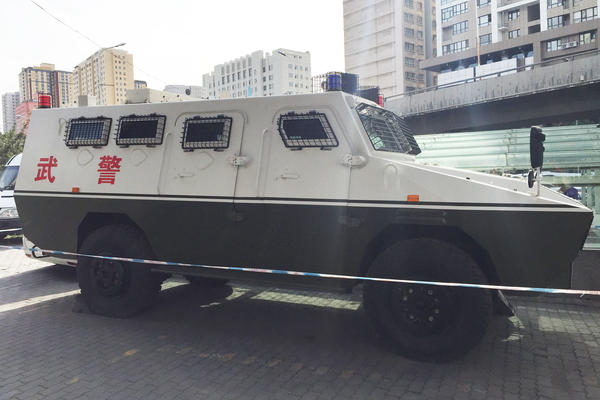 A military police vehicle on a sidewalk in central Urumqi.