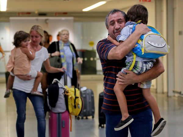 Juan Rojas (right), of Queens, N.Y., hugs his 4-year-old grandson Elias Rojas as his daughter-in-law Cori Rojas (left) carries her daughter, Lilly, 3, through the terminal at JFK airport on Tuesday after they arrived on a flight from San Juan, Puerto Rico. Cori, who is a schoolteacher in Puerto Rico, fled the island with her children after Hurricane Maria left it devastated.