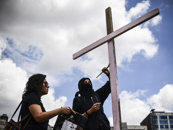 Two women take part in a tribute Sunday to the textile workers killed when their factory was toppled in the earthquake last week in Mexico City.