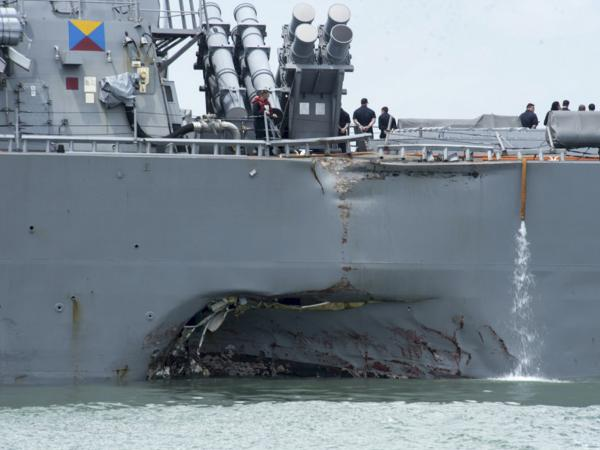 Damage to the USS John S. McCain is visible as the guided-missile destroyer steers toward Changi naval base in Singapore following a collision with the merchant vessel Alnic MC in August.