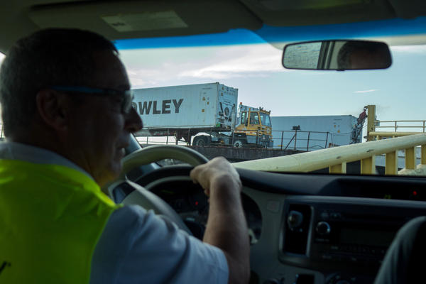 Jose Nazario, Director of Crowley's San Juan terminal operations and administration, drives as containers are unloaded from a barge in the port.