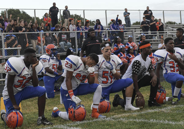 Football players on the Watkins Mill High Wolverines take a knee during the playing of the National Anthem before a game against the Damascus Hornets at Damascus High School in Damascus, Md.