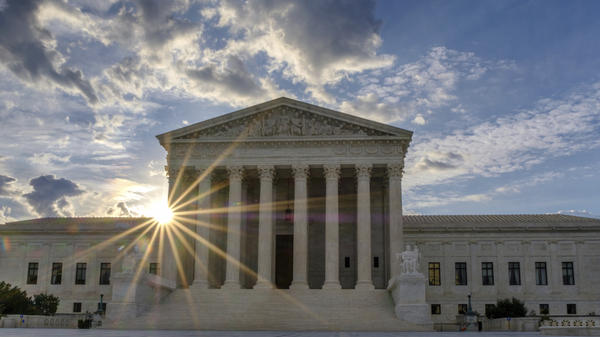 The sun flares in the camera lens as it rises behind the U.S. Supreme Court building in Washington, D.C., on June 25, 2017.