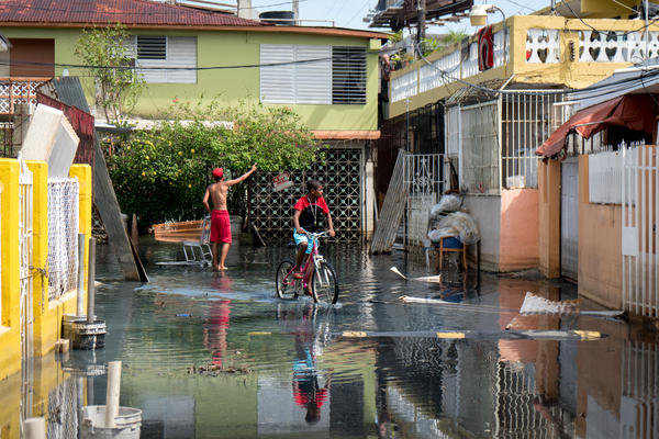 Children walk through standing flood water in the Playita neighborhood. There are small signs that the situation here is improving – but for the residents living through it, the progress is painfully slow.