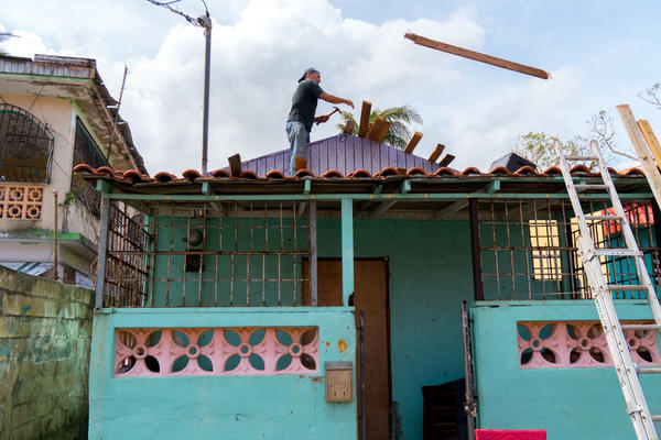 A man's works on his house, which was severely damaged by Hurricane Maria, in San Juan's Playita neighborhood in Puerto Rico. Infrastructure problems that predated the hurricane dramatically worsened the situation in Playita.