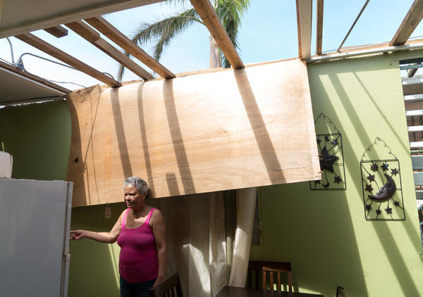 Maria Reyes, 63, stands in her home, which was severely damaged by the storm. She spends most of her time these days caring for her 82-year-old mother, Rafaela.