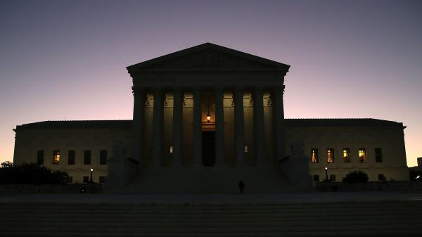 The sun begins to rise behind the U.S. Supreme Court on Monday, the first day of the high court's new session.